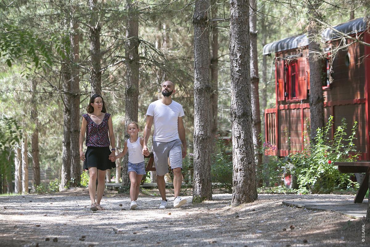 Jeune couple tenant la main de leur fille dans la forêt de pins du parc de DéfiPlanet' - Dienné @S.LAVAL